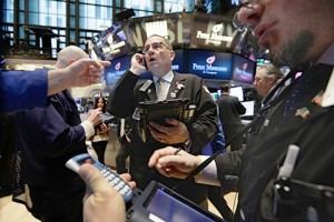 Traders work on the floor of the New York Stock Exchange, Friday, March 20, 2015. Stocks were moving higher Friday as oil prices recovered from their decline the previous day. Strong earnings from restaurant chain Darden and Nike also helped lift the market. (AP Photo/Richard Drew)