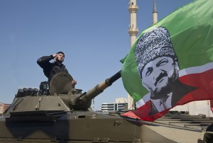 A Chechen special forces officer rides atop an infantry fighting vehicle with a flag portraying Chechen leader Ramzan Kadyrov during Victory Day parade in central Grozny, on May 9, 2013. Fighter jets screamed over Red Square and heavy tanks rumbled over its cobblestones as Russia flexed today its military muscle on the anniversary of its costly victory over Nazi Germany in World War II. Smaller Victory Day celebrations were held on the central squares of cities across Russia as well as at Moscow's Black Sea port of Sevastopol on Ukraine's Crimean Peninsula. AFP PHOTO / ELENA FITKULINA