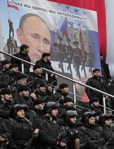 """Chechen special forces listen to Chechnya's regional leader Ramzan Kadyrov deliver a speech as they stand near a banner depicting Russian President Vladimir Putin and words reading """"as long as we are united, we are invincible!"""", in Grozny, Russia, Sunday, Dec. 28, 2014. About 20,000 armed security forces attended a rally at a stadium in Grozny. Kadyrov said that Chechens could serve as """"volunteers"""" to perform military tasks that the Russian armed forces can't fulfill. (AP Photo/Musa Sadulayev)"""