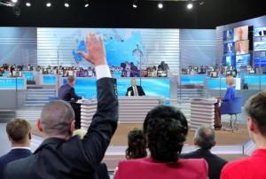 """MOSCOW, RUSSIA. APRIL 14, 2016. Russia's President Vladimir Putin (C background) holds his annual televised question-and-answer session at Moscow's Gostiny Dvor. Mikhail Klimentyev/Russian Presidential Press and Information Office/TASS Ðîññèÿ. Ìîñêâà. 14 àïðåëÿ 2016. Ïðåçèäåíò ÐÔ Âëàäèìèð Ïóòèí (â öåíòíå íà äàëüíåì ïëàíå) âî âðåìÿ åæåãîäíîé ñïåöèàëüíîé ïðîãðàììû """"Ïðÿìàÿ ëèíèÿ ñ Âëàäèìèðîì Ïóòèíûì"""" â Ãîñòèíîì äâîðå. Ìèõàèë Êëèìåíòüåâ/ïðåññ-ñëóæáà ïðåçèäåíòà ÐÔ/ÒÀÑÑ"""