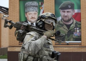 Interior ministry officer walks with a machine gun during exercises in the village of Tsentoroi, 80 km (50 miles) southeast of Chechnya's provincial capital Grozny, Russia, Saturday, April 16, 2016. In the back, portraits of Chechen regional leader Ramzan Kadyrov, right, and his father Akhmad Kadyrov, the Chechen president who was assassinated in a 2004 bomb blast. (AP Photo/Musa Sadulayev)